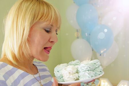 Beautiful woman biting tongue looking at holiday cake. Attractuve woman looking at delicious biscuit cake. Pretty woman going to eat festive Meringue cake. Girl enjoying sweet food