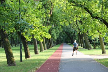 Beautiful city park with treadmill and man running on roller skates. Old man running on roller skates in city park. Urban nature. Healthful lifestyle