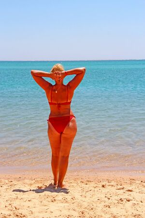 Girl in red bathing suit sunbathing standing on beach by sea. Beautiful woman in red modern swimsuit enjoying rest by sea. 40 years old woman standing on beach during summer holidays