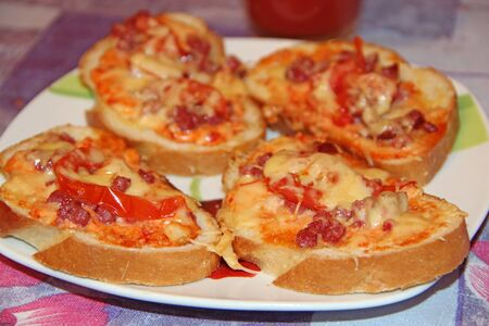 Hot sandwiches with smoked sausage and melted cheese on plate. Delicious fast food 스톡 콘텐츠