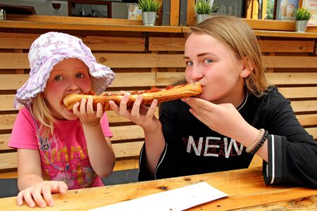 Two girls eat one big sandwich at at the same time. Two sisters eat a delicious sandwich on both sides. Fast food dinner. Childs divide one sandwich. Children eating long burger from different edges 스톡 콘텐츠