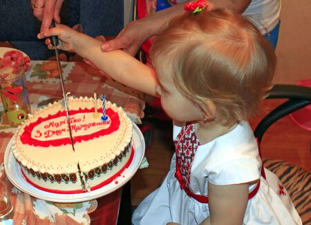 Little girl cutting birthday cake with mother. Cut slice of birthday cake 2 years for small girl. little girl watching her mother cutting tasty cake. festive cake for birthday