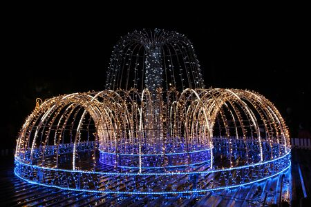 Beautiful fountain of colored holiday garlands glittering and flashing in city park in winter. Christmas and New Years winter holiday lights. City panorama with fontains made from garlands 스톡 콘텐츠