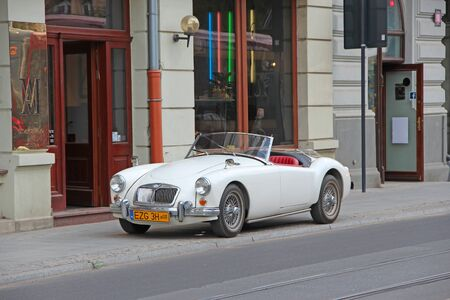 MG car cabriolet on street of Lodz. White auto MG cabriolet standing on curb of city road in Lodz. White 1960 MG MGA convertible roadster parked on city road. Retro car front view