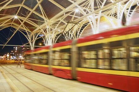 night tram riding around city. Lodz red tram. Modern tram going in movement evening city