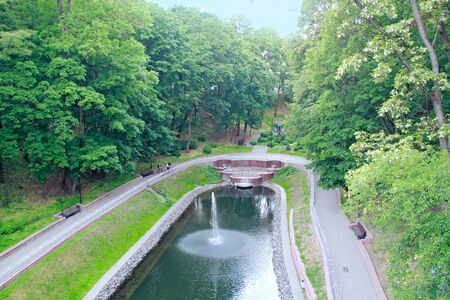 People walk in park with big trees and fountains. Beautiful city park with fountain and pond in Gomel. 스톡 콘텐츠