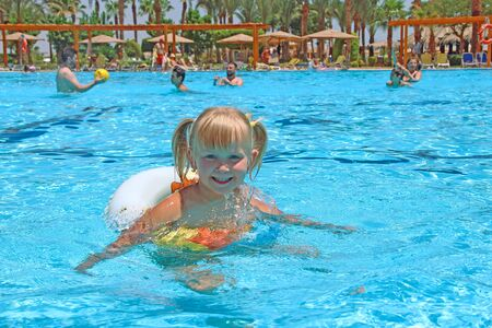 smiling baby girl with nice plaits swimming in swimming pool lying on inflatable circle on summer holidays. Happy childhood. Child relaxing on rubber circle on blue water of pool during holidays