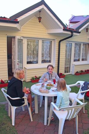 Mother eating with two daughters in yard near house. Gala dinner with children outdoors. Three girls eat dinner by own house