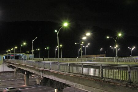 Multiband highway in big city with going cars in night. Cars drive on highway of megalopolis at night. City traffic with lanterns. Intensive traffic on street city. Top view