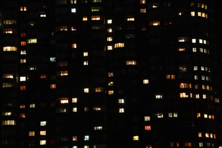 Illuminated multistory houses in night. Night cityscape. Colorful lighting of night metropolis. Many high-rise buildings. Night panorama of light in windows of multistory building. Life in big city