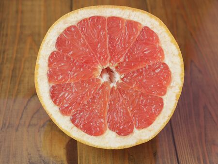 Ripe slice of pink grapefruit citrus fruit on wooden background. Red grapefruit ready to eat. Ripe cut citrus. Sliced grapefruit on brown background. Useful food