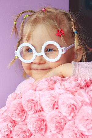 Little girl in plastic glasses smile near paper flowers made from papier-mache. Portrait of baby with pigtails and glasses without glass. Childish smile. Young girl wearing sunglasses. Fashion little child. Human expression