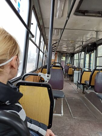 woman in protective mask riding in empty trolley bus during quarantine due to coronavirus. The only passenger in public transport taking care of health during COVID-19 epidemic