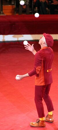 Merry clown amusing audience in circus arena. Funny clown having fun in circus. Merry clown giving smile and good mood