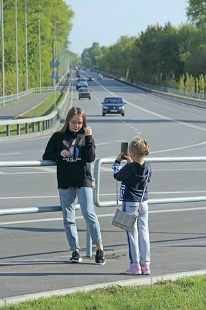 Little girls take pictures of each other near the highway. Sisters take a photo for memory. Children take a photo near the road. Happy children taking selfie near modern motorway by smartphone Reklamní fotografie