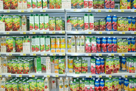 juices on supermarket shelves. Natural juices on shelves of shop. Different fruit juices on shelves in supermarket. Various juice in paper package
