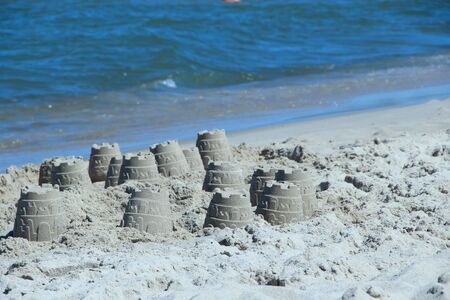 Sandy pyramid on the seashore. Sand pyramid built on the seaside. Childish works. Sand houses built by children by the sea. Summer holidays. Relaxing concept. Rest by Baltic sea