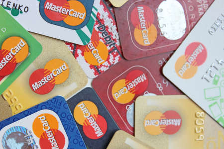 different credit cards with Mastercard brand logo. Close up of many Mastercard credit cards. Plastic bank cards of Mastercard. International payment systems