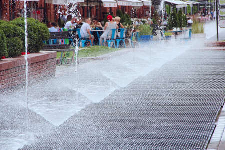 people have a rest near city fountains. Jets of water at fountains in hot summer day. Row of fountains in city 版權商用圖片