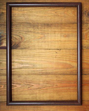 Brown frame on wooden background. Dark frame on wooden texture. Old grunge dark texture. Frame for photo. Foto de archivo
