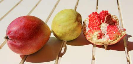 Ripe pomegranate pear and mango close up. Delicious fruits. Useful food. Health care. tropical fruits. Set of fruits close-up. Pomegranate mango and pear