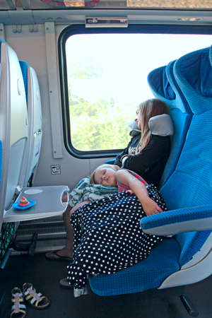 Children sleep in soft-seated carriage of train during the trip. Children sleep in electric train chairs while traveling. Sleeping children. People sleep in train car. Family trip. Tired children