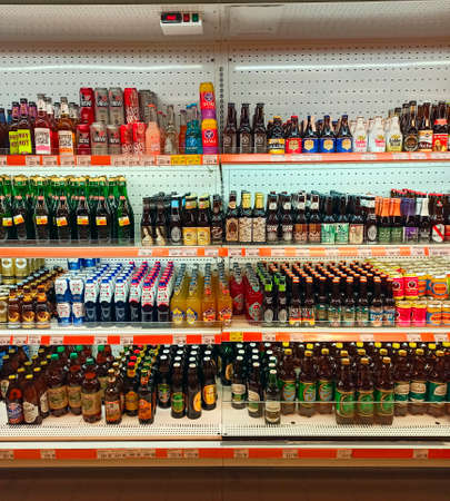different kinds of beer and soft drinks like pepsi-cola with wide assortment on the shelves of supermarket Редакционное
