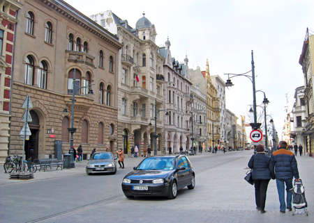 City life in Lodz. Busy traffic on streets of Polish city of Lodz. Transport and city life in Poland. Urban panorama with beautiful architecture and cars Редакционное