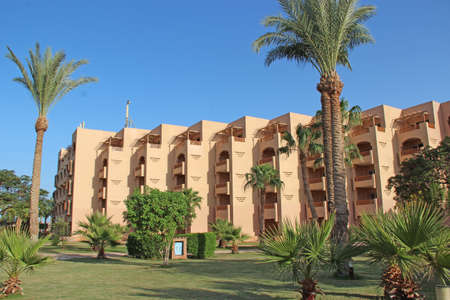 Tropical resort in Egypt. People swimming in sea. Tourists relax on beach. People enjoy vacations on seaside resort at Red sea. Rest in Hurghada hotel Egyptian resort Редакционное