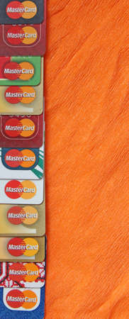 different credit cards with Mastercard brand logo. Close up of many Mastercard logos on credit cards. Plastic bank cards of Mastercard. International payment systems Редакционное