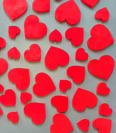 Red hearts hanging on wall. Textured symbol of love. Red hearts decoration on wall. Gift for Valentine day. Shaped hearts hang on wall. interior design
