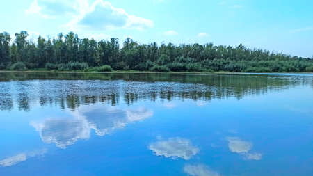 Landscape with spring river. Trees and bushes are reflected in water of river. Spring forest. Water surface of forest river. Beautiful spring landscape. Travel concept. Reflection of sky in water
