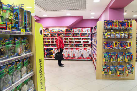 Shop toys. Toy store. Inside toy shop. Rows of shelves with toys. Children's joy. Man choosing toy among wide selection in children's store. Shop for children Редакционное