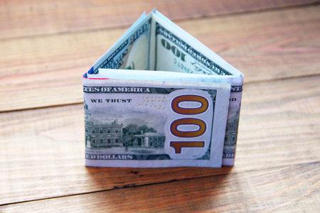 Hundred dollar notes on wooden boards. Hundred dollar bills folded in triangular shape. Money in cash