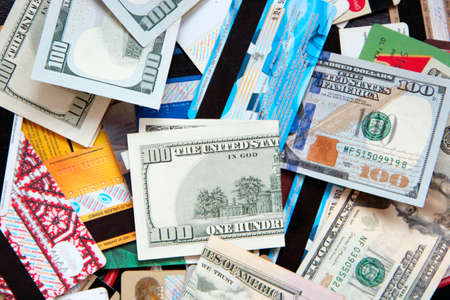 Banknotes with credit cards. Cash and non-cash money. US dollars. Fifty dollars and pile of credit cards. Heap of money and credit cards. Wealth. Material values