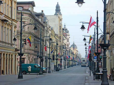 City life. Traffic on street of Polish city Lodz. Crossroads on busy city street. People wait for traffic light to cross street. City panorama with beautiful architecture. Street in Polish town Редакционное