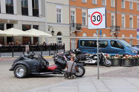 Stylish transportation outdoors. Biker motorcyclist. Cool transport. biker sitting near motorcycle. Stylish man sitting near motorcycle. Unusual motorcycles stand on Warsaw street