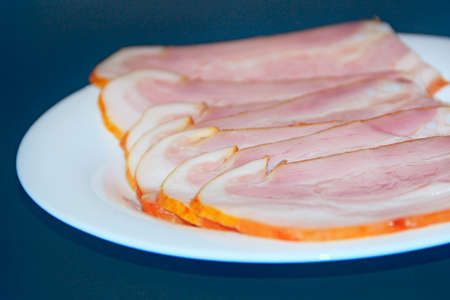 Sliced smoked meat on white plate. Thin slices of sliced bacon. Plate of thin slices of ham. Food appetizer concept. Pork ham sliced. Baked ham with slices on plate on black background