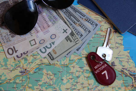Passports and room keys. Travel concept. Things collected for travel. Personal items for holidays. Map and number key seven. Room key from dwelling during summer vacation. Money for trip Фото со стока