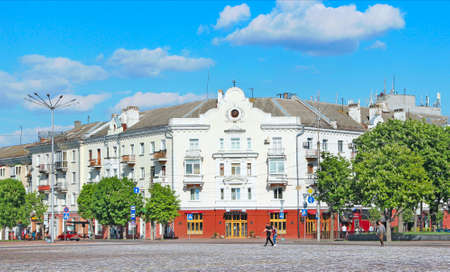 City square with blossoming chestnuts. Central area in Chernihiv town with beautiful view to buildings. People walk on square in city of Chernihiv. Spring in city. Cityscape