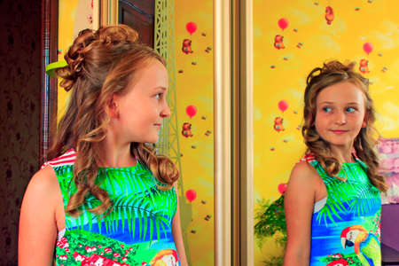 girl with lush hairstyle poses in front of mirror. Portrait of girl in front of mirror. Smart child. Children hairstyle. Reflection in mirror. Girl with modern hair do