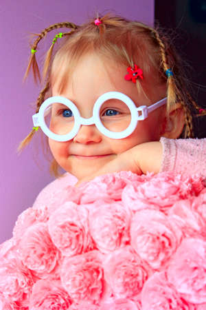 Little girl in plastic glasses smile near paper flowers made from papier-mache. Portrait of baby with pigtails and glasses without glass. Young girl wearing sunglasses. Portrait of child