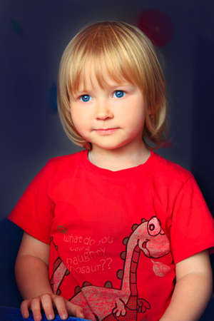 Portrait of little girl with blond hair on dark background. Child's face in dark. Portrait of girl from darkness. Portrait of baby. Child with light hairs and blue eyes