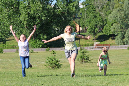 Happy mother having fun jumping with her daughters on green grass. Happy family team. Family enjoying summer vacations. People enjoying family holiday Фото со стока