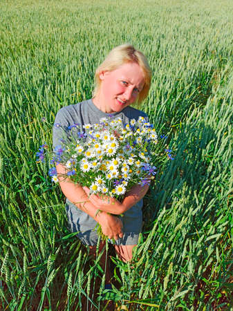 Portrait of woman with bouquet of camomiles and cornflowers in wheat field. Portrait of rural woman with flowers. Woman with bouquet of white field daisies