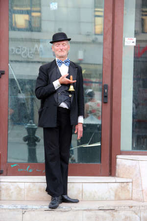mime artist showing frozen statue on street. Man in hat with hand bell in hands. Fun character making living outdoors shows. Man earning his life playing part outside