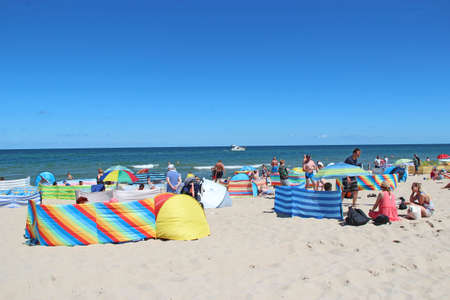 People relax on beach of Baltic Sea during summer vacation. Baltic Sea coast with vacationers. Family holidays on Baltic Sea. Summer holidays on seaside