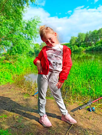 little girl standing near river. Child playing about. Portrait of little girl standing in strange pose. Little girl posing outdoors during fishing Фото со стока