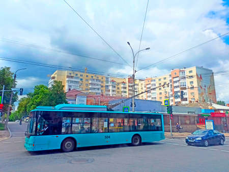 trolley bus riding along city street. Busy traffic in Chernihiv town. Urban transport and cars. Public transport on street of city. Blue trolleybus driving down street