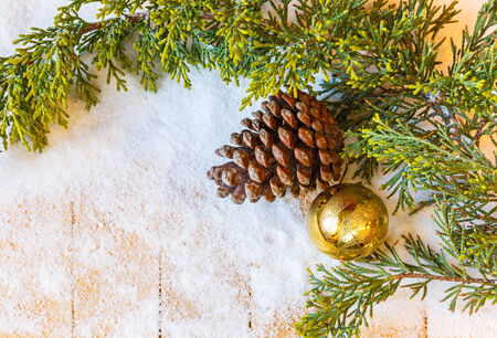 Christmas tree branch, pine cones and fir-tree toy in the snow photo